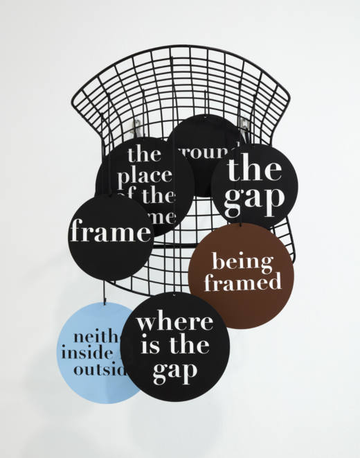 C.Hang.Frame.Grid (Bertoia)…oh no…, 2019. Bertoia wire chair (black), acrylic paint, text on different aluminium elements (different shapes), wire. 73,3 x 54 x 57 cm. Cortesía del artista y Galería Helga de Alvear, Madrid.